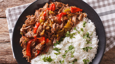 Cuban cuisine: ropa vieja meat with rice garnish on a plate  close-up. Horizontal view from above