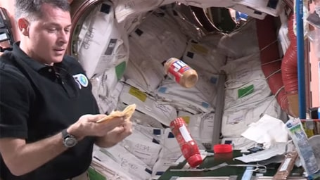 NASA astronaut making a peanut butter and jelly sandwich in space