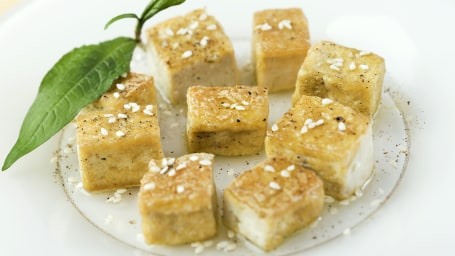 Fried tofu cubes arranged on plate, garnished with sesame seeds