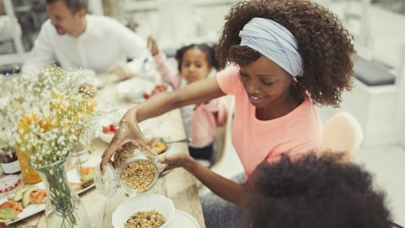 Mother pouring granola cereal for daughter at breakfast table