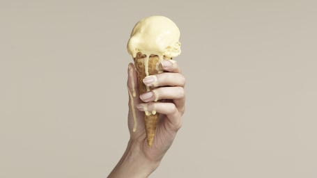 Woman holding melting ice cream cone