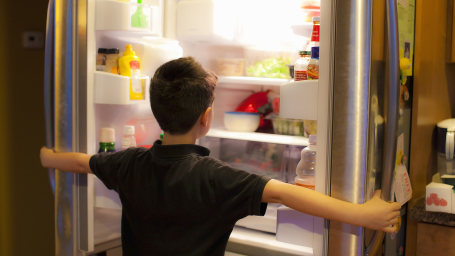 Asian boy searching through refrigerator