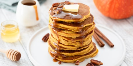 Pumpkin spice pancakes stack on white plate