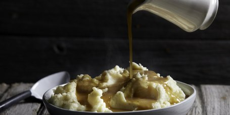 Jug of gravy being poured onto bowl of steaming mashed potatoes, studio shot
