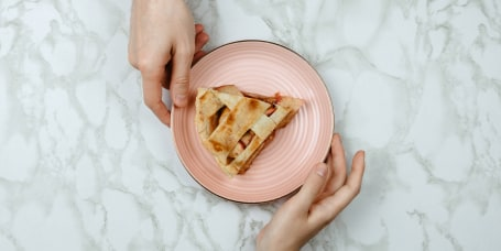 Flatlay of men passing the piece of apple pie to woman's hand on marble background