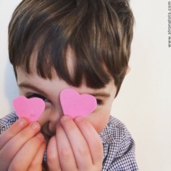 Boy holding hearts up in front of his face