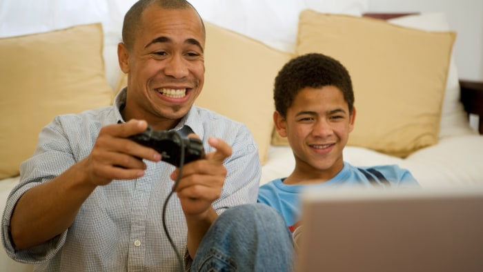 Image: Image: Image: Father and son playing video game