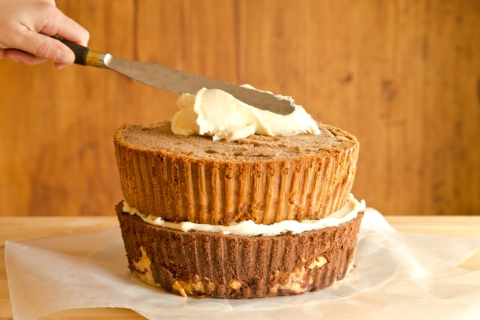 How to Make The Cherpumple Step-by-Step: Scoop 1 heaping cup of frosting onto the center of the pumpkin-pie-spice-cake layer and spread to the edges in a wide circular motion with a large icing spatula or knife