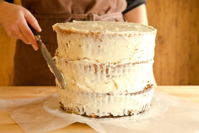 "How to Make The Cherpumple Step-by-Step: Apply a thin layer of frosting around the sides of the Cherpumple to ""crumb coat""—this layer seals in any stray crumbs so they won't be visible on the finished cake."