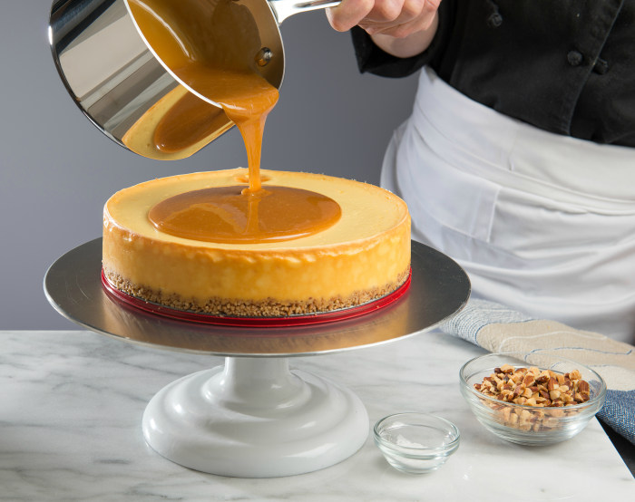 Pouring caramel on the Salted Caramel Flan Cheesecake; recipe courtesy of Eli's Cheesecake