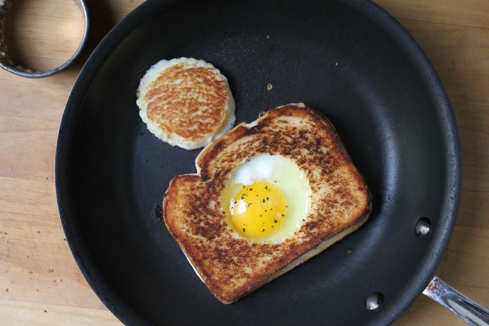 Grilled Cheese Egg-in-a-Hole: Melt 1 teaspoon of butter in the hole. Crack the egg into the hole and sprinkle with salt and pepper.