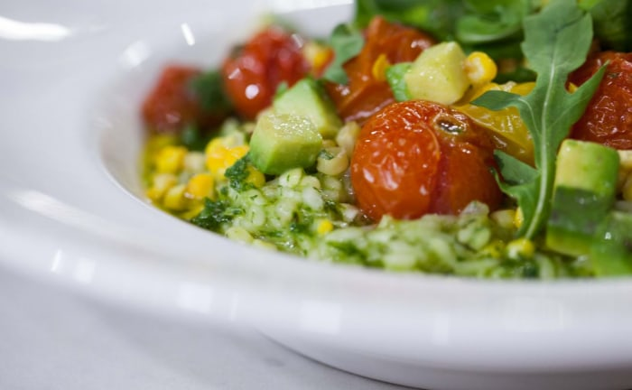 Healthier risotto with tomato, corn and arugula basil pesto