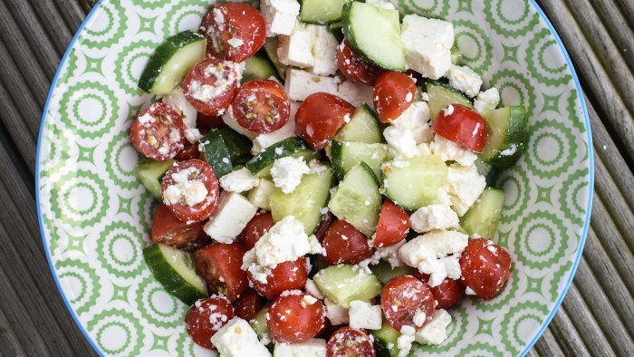 Greek Salad with tomato, cucumber and Feta cheese on a white and green plate.
