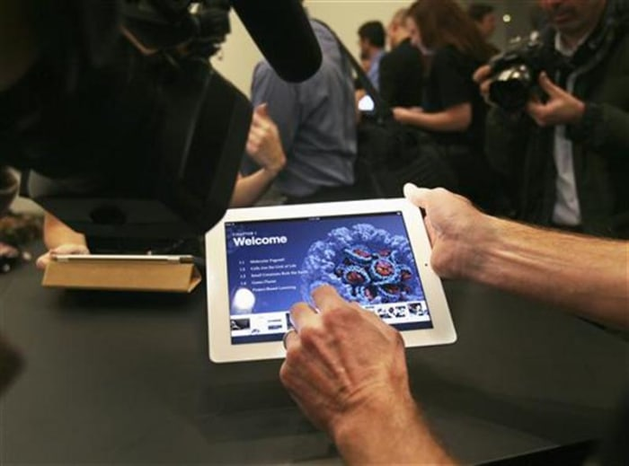 A man shows an example of an iBook textbook on an iPad after a news conference introducing a digital textbook service in New York
