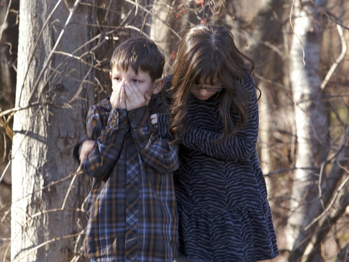Young children wait outside Sandy Hook Elementary School after a shooting in Newtown, Connecticut, December 14, 2012. A shooter opened fire at the ele...