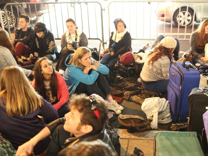Dedicated mom: Patty Bousetta, center left in blue jacket, sits in the blocked off area for the One Direction near Rockefeller Center the evening befo...