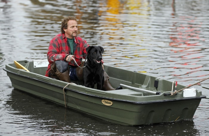 Ray Cilli and his dog Woubie are rescued from flood waters brought on by Sandy in Little Ferry, N.J., on Tuesday.
