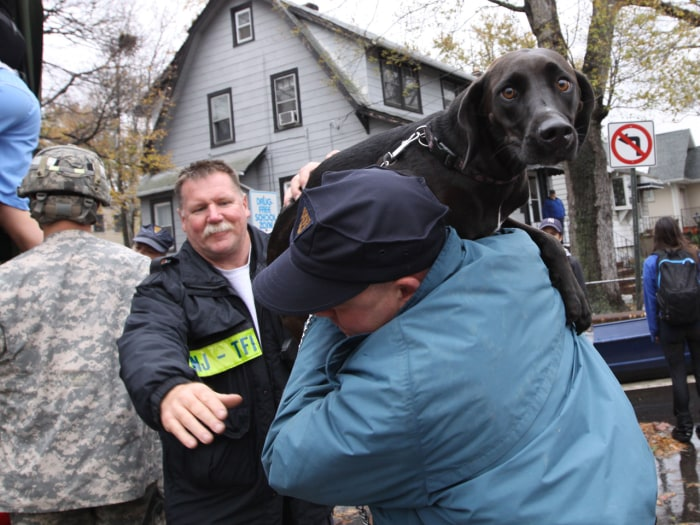 A resident and his dog are evacuated on Tuesday from a neighborhood in Little Ferry, N.J., one day after the superstorm Sandy slammed the East Coast.