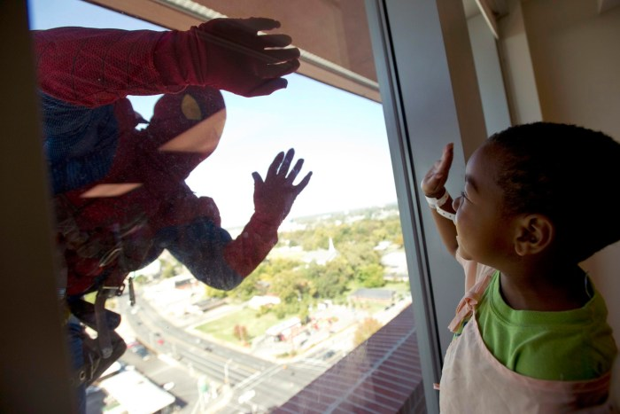 Dressed as Spiderman, a window washer with American National Skyline greets Le Bonheur Children's Hospital patient Orlando Farmer, 3, as he rappels do...