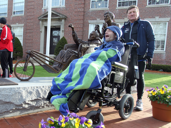 Dick Hoyt, right, and his son, Rick, stand next to a statue honoring them near the start of the 117th running of the Boston Marathon, in Hopkinton, Ma...