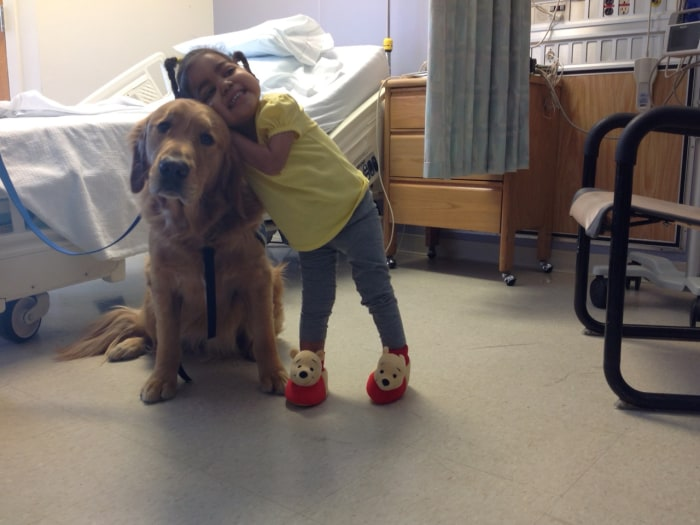 Image: Yenni Campusano, age 2, with a comfort dog