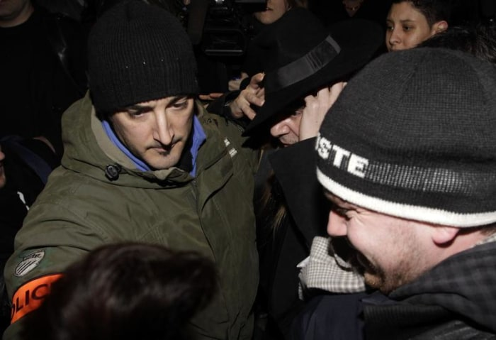 Image: Fashion designer John Galliano is surrounded by police
