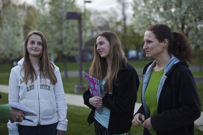 Students Sarah Lachenmayr (L), Samantha Rieche (C) and her mother Anne Rieche arrive to attend a school board meeting in Readington Township, New Jersey, April 23, 2013.