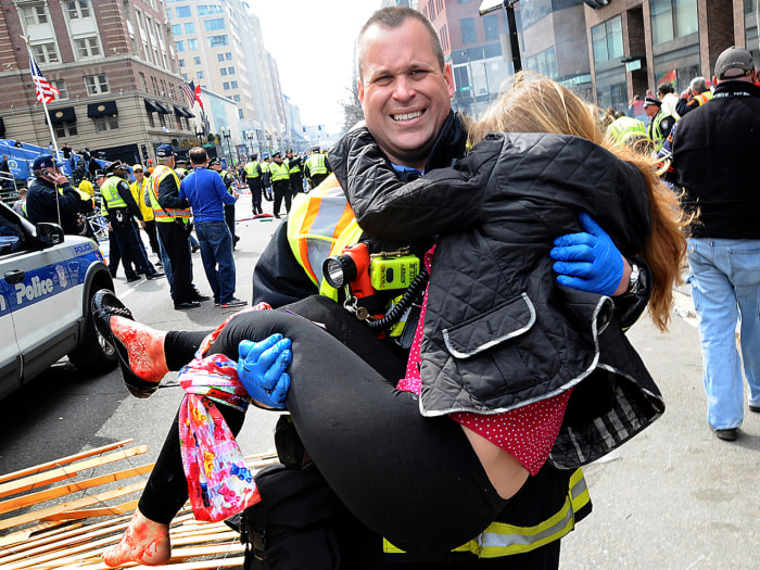 In this Monday, April 15, 2013 photo, Boston Firefighter James Plourde carries an injured girl away from the scene after a bombing near the finish lin...