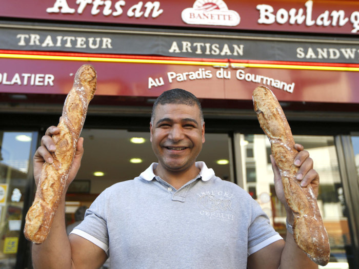 Parisian baker Ridha Khadher, winner of the Best Baguette of Paris 2013 award, holds his baguettes, French bread, as he poses in front of his bakery a...