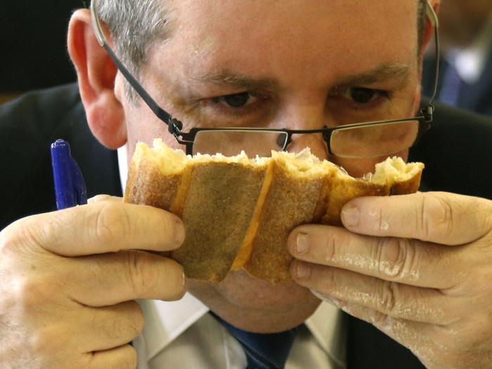 Jury member Pascal Barillon, winner of the 2011 Paris Best Baguette award, sniffs a baguette, French bread, in competition for the 'Grand Prix de la B...