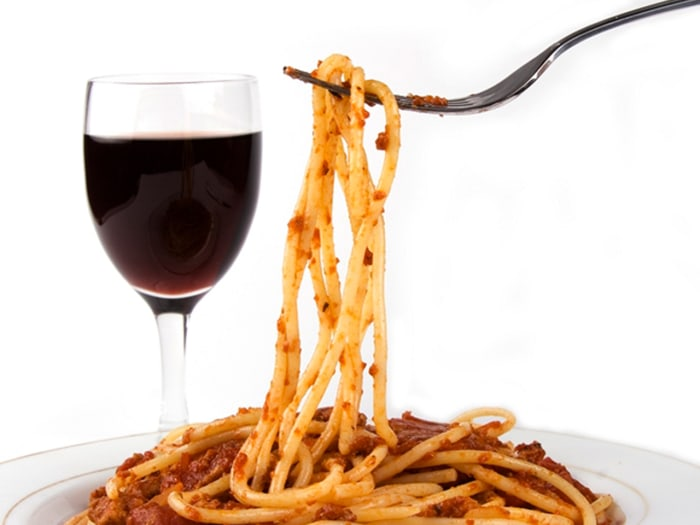 Spaghetti with red wine in isolated white background.