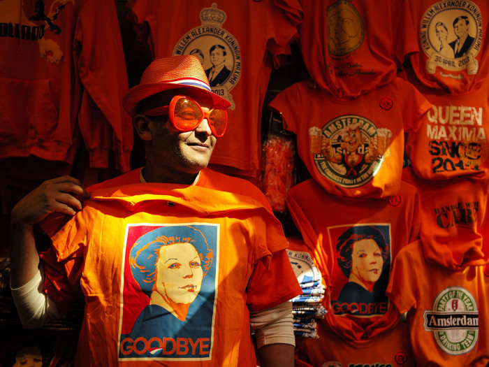 A man wearing shades displays a t-shirt depicting Dutch Queen Beatrix in a souvenirs shop in Amsterdam April 29, 2013. The Netherlands is preparing fo...