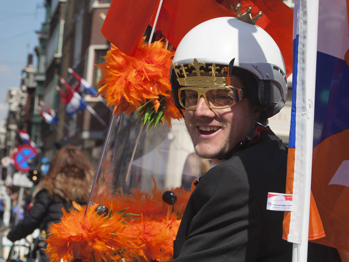 A man riding a scooter and wearing a crown on a helmet cruises the streets of Amsterdam April 28, 2013. The Netherlands is preparing for Queen's Day o...