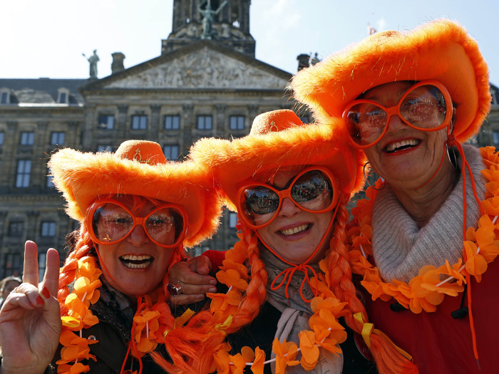 Visitors from Sydney, Australia wearing the Dutch national colors pose for photographers outside the Royal Palace in downtown Amsterdam, Netherlands M...