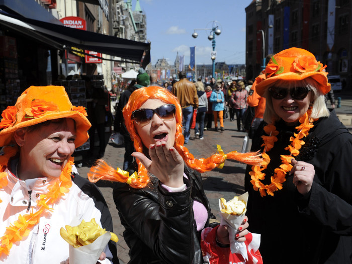 epa03681162 Tourists wear funny 'Oranje' (orange) headgear in anticipation of the upcoming investiture of the country's new King, in Amsterdam, The Ne...