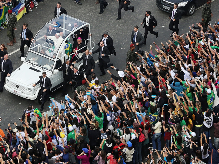 Pope Francis waves from the Popemobile as he arrives to celebrate Mass on Copacabana beach.