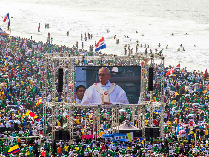 Pilgrims watch Pope Francis on a video screen as he celebrates mass on Copacabana Beach in Rio de Janeiro.