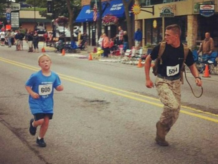 Lance Corporal Myles Kerr helps 9-year-old Boden Fuchs across the finish line.