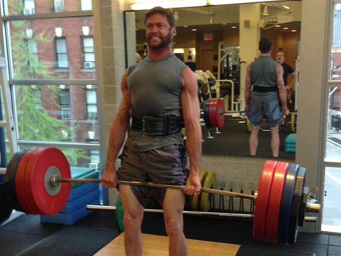 A ripped Hugh Jackman lifts (many) weights.