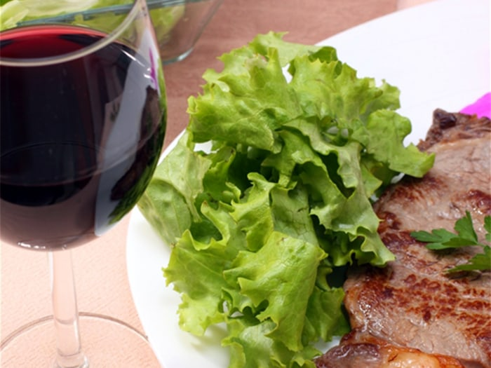 a white platter with beef steak and lettuce