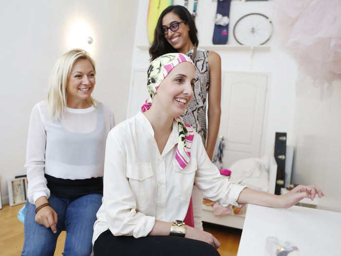 Fashion designer Ashley Granata, shown in her Brooklyn studio with clients,  recently launched a one-for-one scarf business for cancer patients.