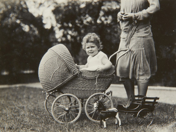 A 2-year-old Princess Elizabeth poses for the camera while sitting in a wicker pram in 1928. The photos were taken by her father, King George VI when he was the Duke of York.