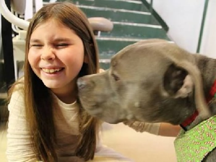 Emma Wishneski, a third grader who was at Sandy Hook last year, and her therapy dog Jeffrey