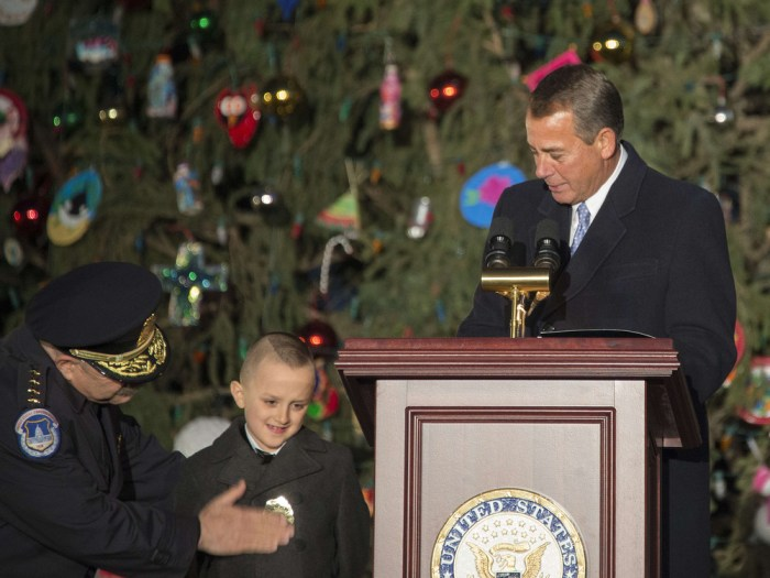 U.S. Speaker of the House John Boehner watches as 6-year-old Giovanni Gaynor is made an honorary Capitol police officer by U.S. Capitol Police Chief Kim Dine, left, before lighting the Capitol Christmas Tree on Tuesday.
