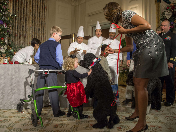US First Lady Michelle Obama (R) pulls on her dog Sunny as two-year-old Ashtyn Gardner reacts during the White House Christmas decorations viewing at ...