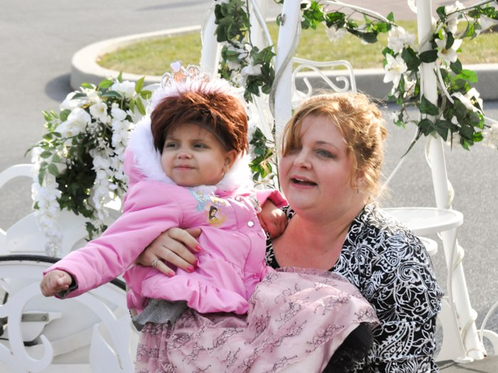 Image: Brielle's mother, Tina Kelly, carries her daughter from the horse-drawn carriage to the party.