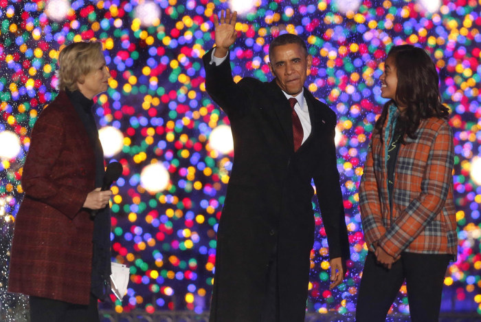 President Barack Obama waves as he stands with daughter Malia and actress Jane Lynch at the the National Christmas Tree lighting ceremony across from ...