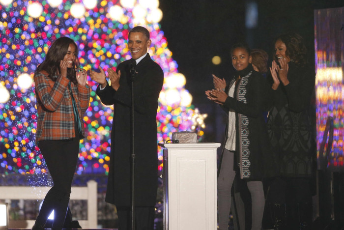 President Barack Obama, first lady Michelle Obama, daughters Sasha and Malia, applaud after lightng the National Christmas Tree at a ceremony across f...