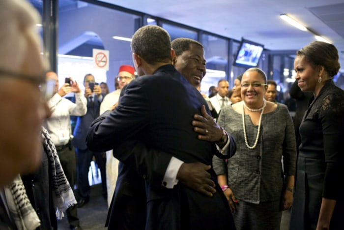 President Yayi Boni of Benin welcomes President Obama as he arrives at the soccer stadium for the Nelson Mandela memorial service.