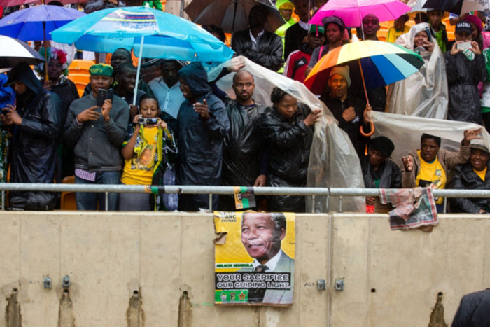 South Africans protect themselves from the rain at the memorial service for Nelson Mandela.